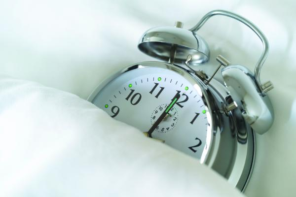 photo of alarm clock in bed